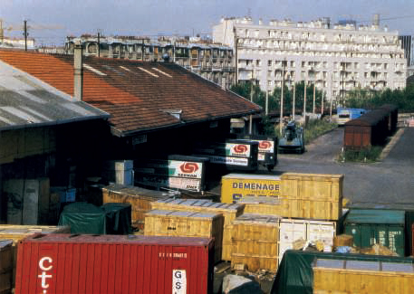 Reuilly, 5 août 1984, la gare marchandises est bien active au vu de ces nombreux cadres et caisses et camions du Sernam. En arrière-plan, des wagons couverts à bogies Gas 8.16 se trouvent sur une voie en impasse, à proximité d'une grue Griffet.